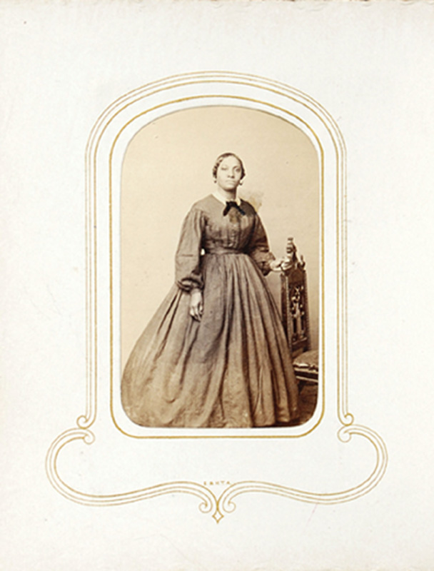 1.22. Woman standing with chair. Percival, NYC. CDV.